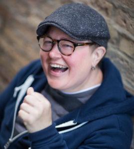 Comedian Maggie Faris against a brick wall